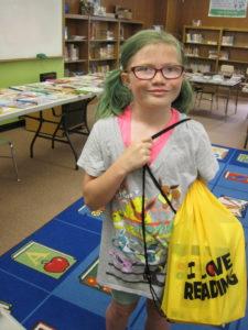 Second grade girl holding back pack full of books